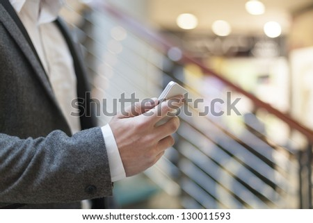 Man with smart phone on hand, blurred background, business building interior - stock photo