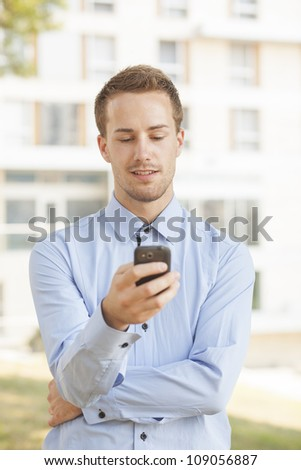 Man with smart phone on hand, business building - blurred background - stock photo