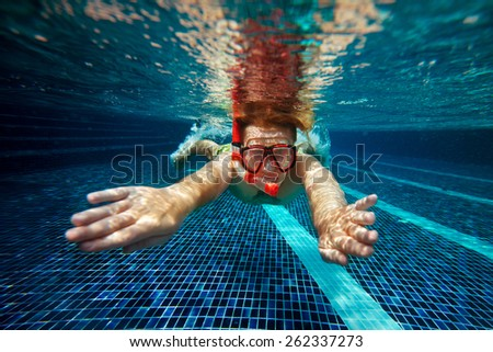 Man with snorkel mask and tube swim underwater in swimming pool  - stock photo