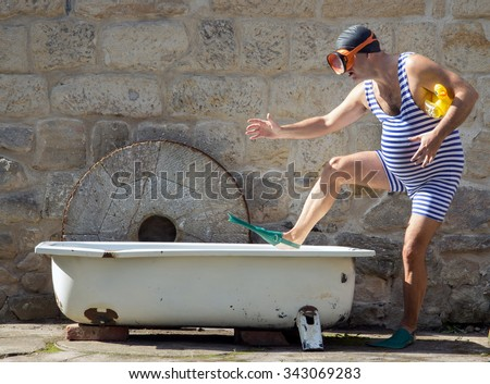 Man with snorkeling gear going to the bathtub outdoor. Funny man in a retro swimsuit goes to a tub with an inflatable toy - duck. Man with diving goggles step to bathtub. Bath a childish man. - stock photo