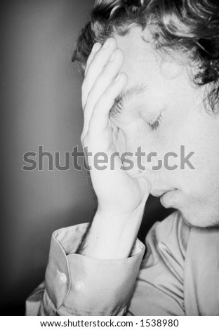Man with sorrowful look and his hand over his face, touching his forehead - stock photo