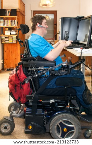 Man with spastic infantile cerebral palsy caused by a complicated birth sitting in a multifunctional wheelchair using a computer with a touch screen and wireless headset, side view - stock photo