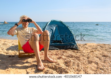 Man with spy glasses camping at the beach - stock photo