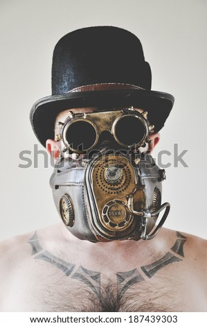 Man with steampunk hat, goggles and mask. These are parts of my steampunk costume which I made for a party. Vintage toned. - stock photo