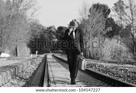 Man with suit , hat and suitcase walking across the railway - stock photo