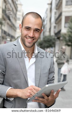Man with suit jacket using touchpad in town - stock photo