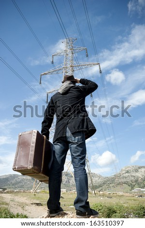 Man with suitcase in a field - stock photo