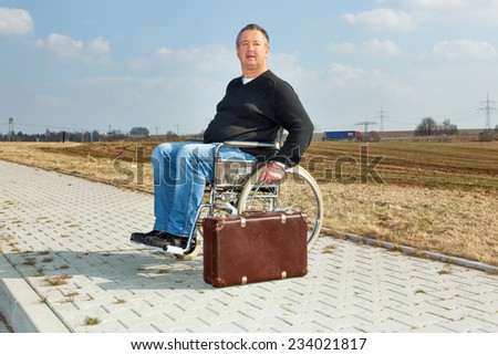 Man with suitcase wheelchair and walk on the road - stock photo