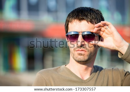 Man with sunglasses standing outdoor - stock photo