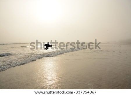 Man  with surfboard on the beautiful foggy beach. - stock photo