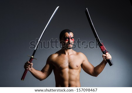 Man with sword and face paint - stock photo