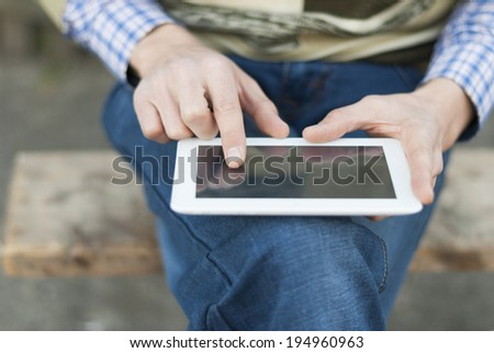Man with tablet in hand on the street. - stock photo
