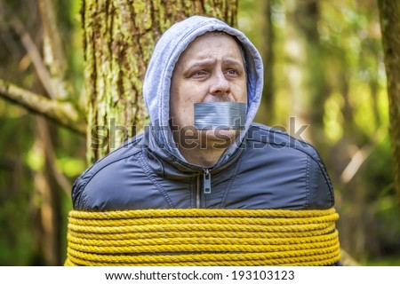 Man with tape on mouth tied to the tree in the forest - stock photo
