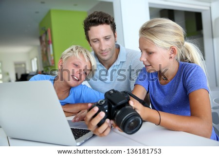 Man with teenagers looking at pictures on computer - stock photo