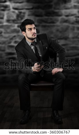 Man with the smart phone sitting on the chair and looking up - stock photo