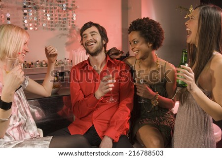 Man with three women at a nightclub. - stock photo