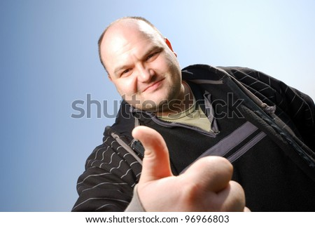 man with thumb up in front of blue sky - stock photo