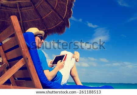 man with touch pad on tropical beach - stock photo