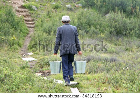 man with two bucketful of water - stock photo