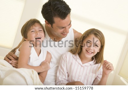 Man with two young children sitting in bed smiling - stock photo