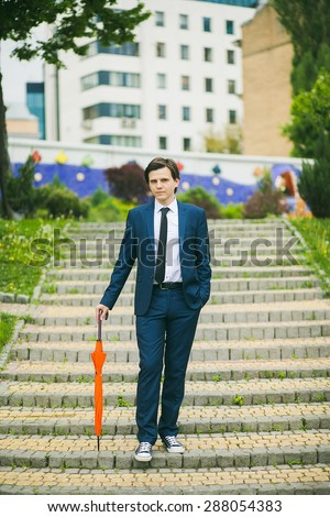 Man with umbrella in hands. Portrait of man in suit. Positive man standing outdoors at city landscape. - stock photo