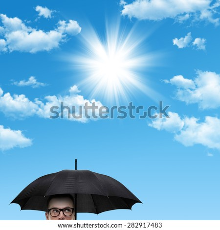 Man with umbrella over blue sky with some clouds and sunshine - stock photo