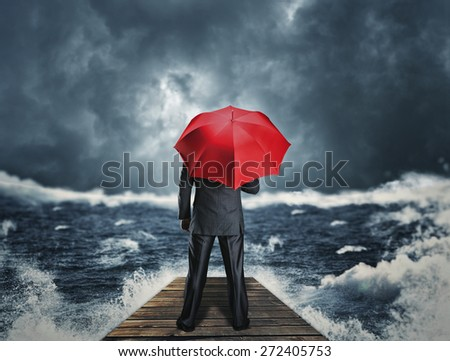 Man with umbrella standing on the pier - stock photo