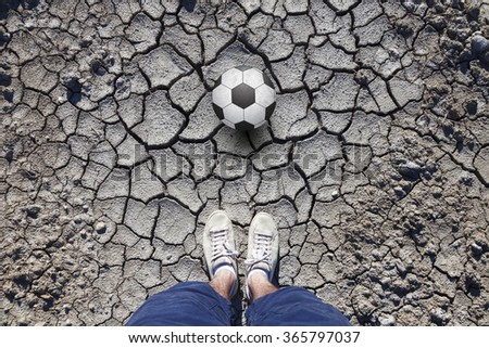 Man with white shoes standing on cracked dried soil ground with a soccer ball. Conceptual soccer ball game photo. Point of view man standing on cracked soil ground with a soccer ball. - stock photo