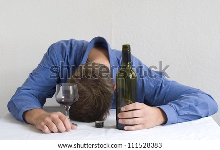 Man with wine bottle and glass, sleeping on the table. - stock photo