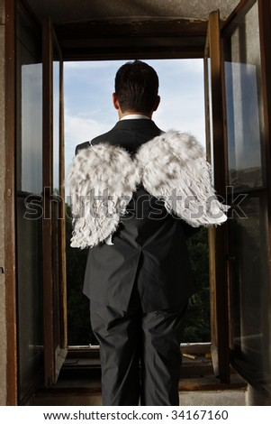 man with wings looking out of the window - stock photo