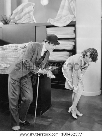 Man with woman pointing at run in stocking - stock photo