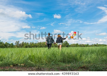 Man, women, Asian green meadow with colored balloons. - stock photo