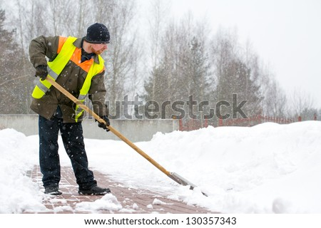 Man worker in uniform shoveling snow - stock photo