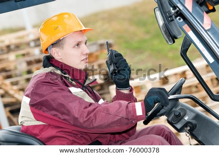 man worker sitting in industrial stacker forklift at warehouse using radio transmitter - stock photo