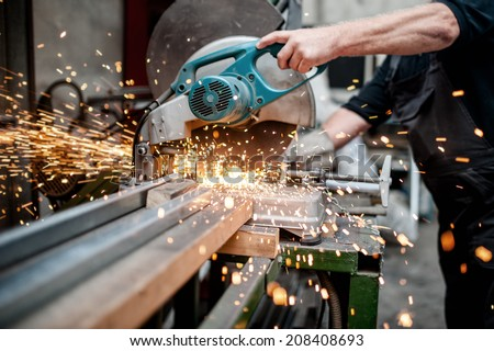 man, worker using a sliding compound mitre saw with circular blade for cutting meta - stock photo
