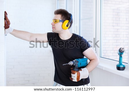 Man worker with drill. Bright white colors. - stock photo