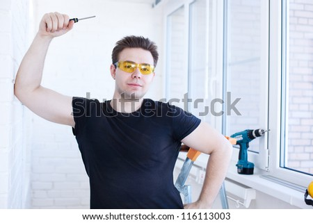 Man worker with screwdriver on balcony. - stock photo