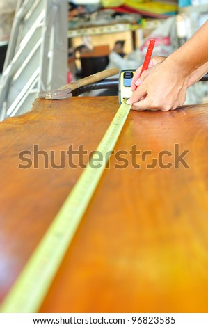 man working and measuring  wood - stock photo