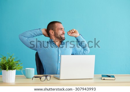 Man working at desk in office stretching his back at desk - stock photo
