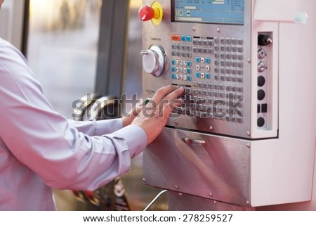 Man working at programmable machine - stock photo