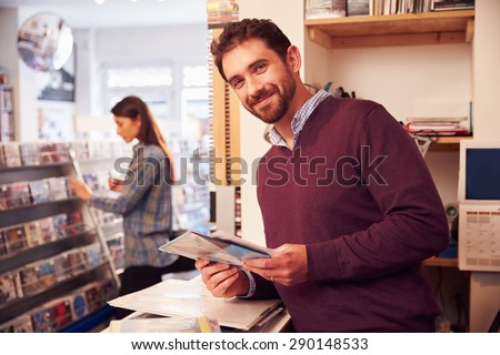 Man working behind the counter at a record shop, portrait - stock photo
