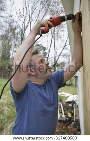 Man working construction job holding drill wearing blue t-shirt - stock photo