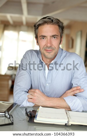 Man working from home with tablet and agenda - stock photo