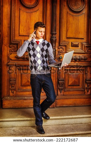 Man Working Hard. Wearing a patterned sweater, red tie, blue jeans, leather shoes, a young guy is waling down from office, talking on his mobile phone, working on a laptop computer in the same time. - stock photo