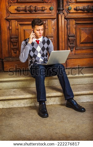 Man Working Hard. Wearing patterned sweater, red tie, blue jeans, leather shoes, a young guy is sitting on stairs by office door, talking on mobile phone, working on laptop computer in the same time. - stock photo