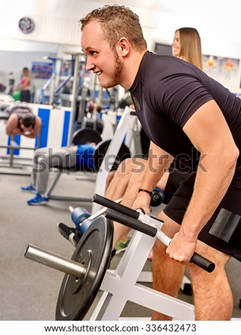 Man working his arms and back at gym. He lifting very heavy barbell. - stock photo