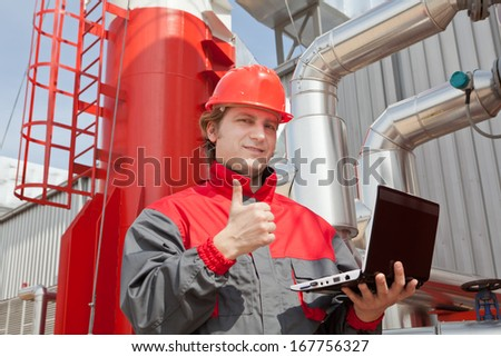 Man working in a factory, controls the operation of devices in a Heating Plant or Refinery. Please see my other photo and videos with the same theme.  - stock photo