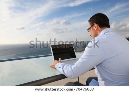 Man working in front of the sea during vacation time - stock photo