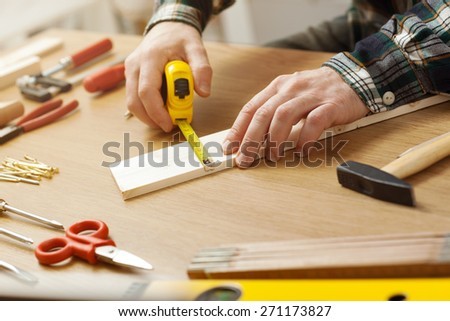 Man working on a DIY project and measuring a wooden plank with work tools all around, hands close up - stock photo