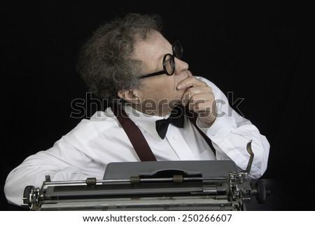 Man working on a vintage typewriter/Author Working on Typewriter/Man with glasses working on typewriter - stock photo